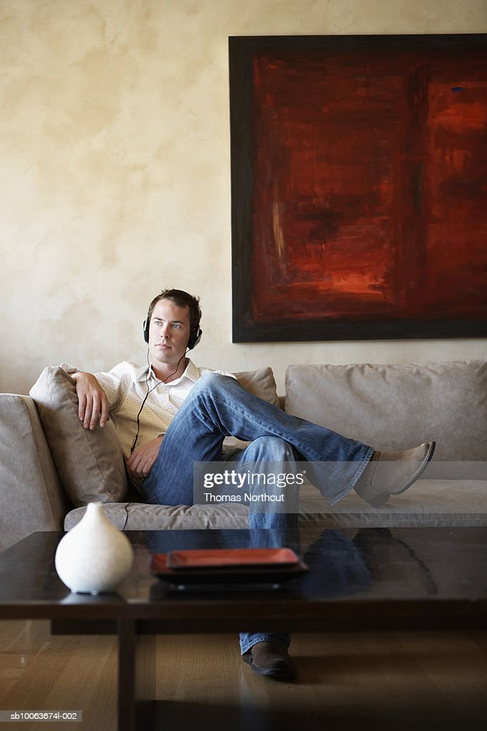 Young man sitting on sofa wearing headphones : Stock Photo