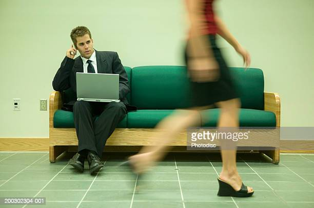 Young man sitting on sofa with laptop and mobile phone, woman passing by