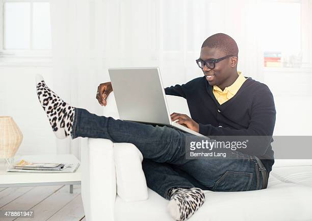 Young man sitting on sofa with laptop computer