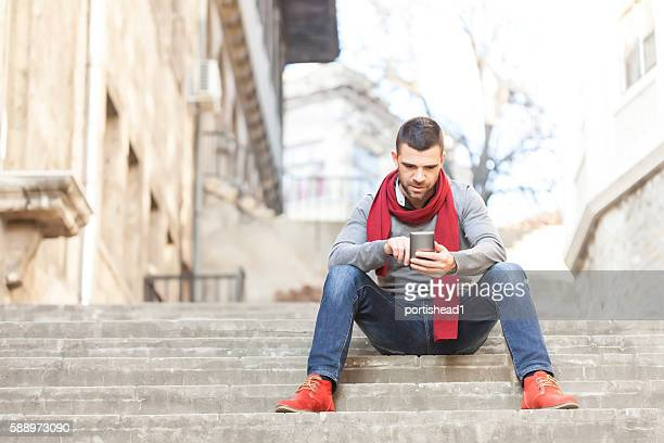 Young man sitting on stairs and using smart phone