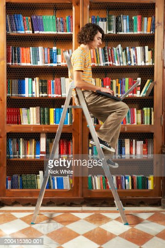Young man sitting on step ladder in library using laptop, side view : Stock Photo