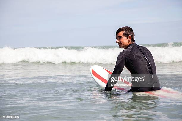 Young man sitting on surfboard in sea