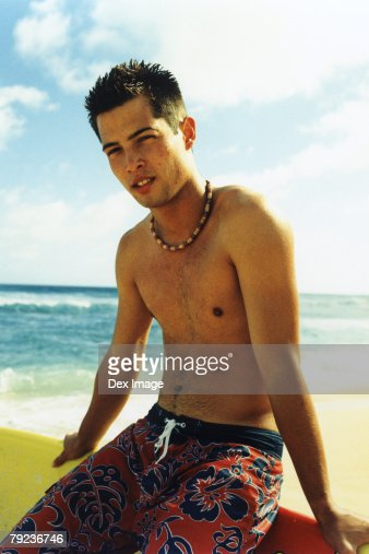 Young man sitting on surfboard : Stock Photo