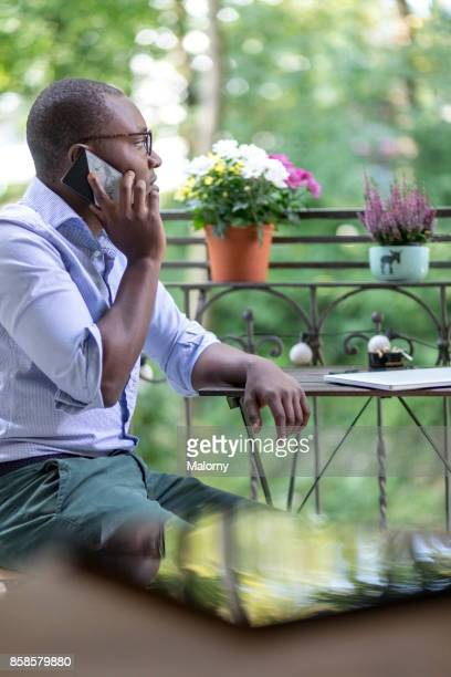 Young man sitting on the balcony, using his phone. Home office.