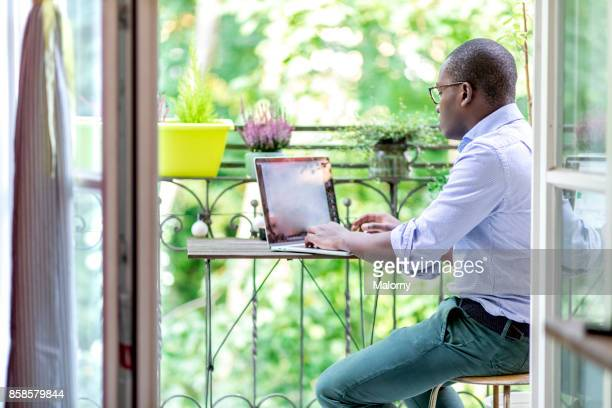Young man sitting on the balcony, working on his laptop. Home office.