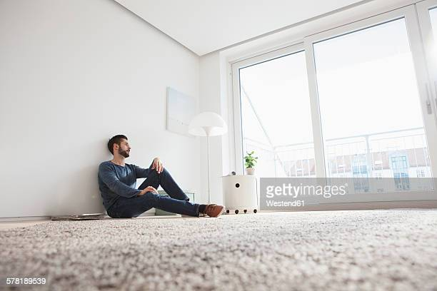 Young man sitting on the floor of living room looking through window