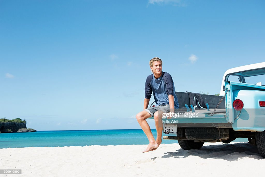 Young man sitting on trailer on beach : Bildbanksbilder
