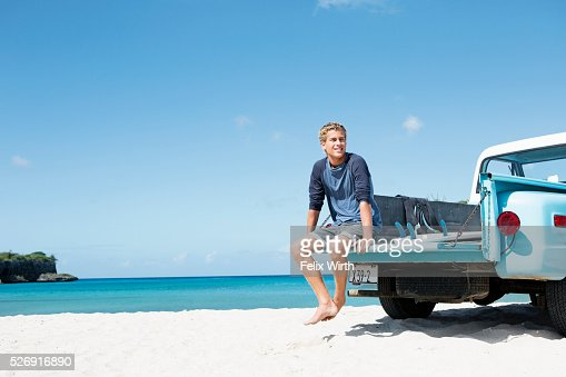 Young man sitting on trailer on beach : Stock Photo