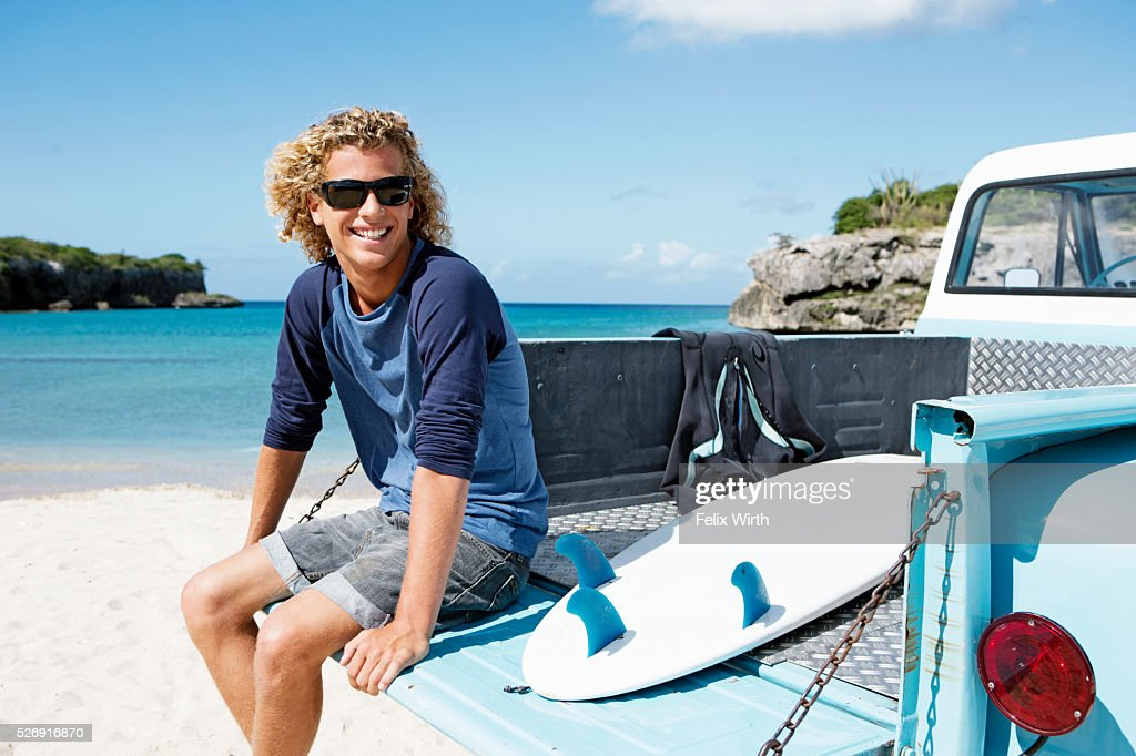 Young man sitting on trailer with surfboard : Bildbanksbilder