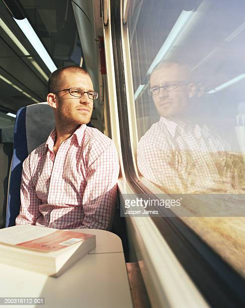 Young man sitting on train looking out of window