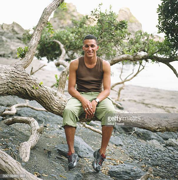 Young man sitting on tree branch on beach, portrait