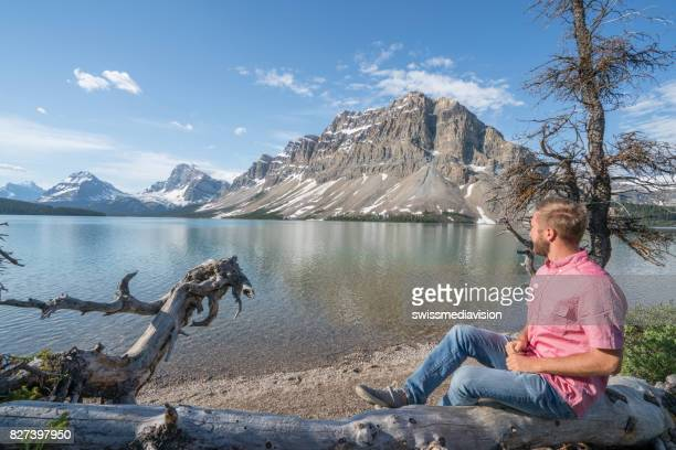 Young man sitting on tree trunk at mountain lake