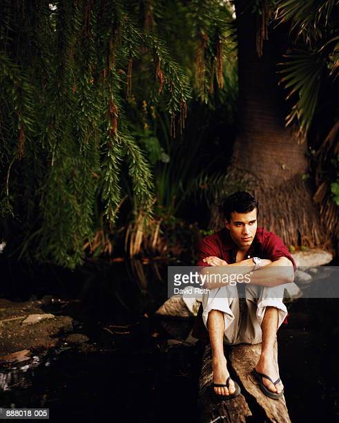 Young man sitting on tree trunk, with pensive expression