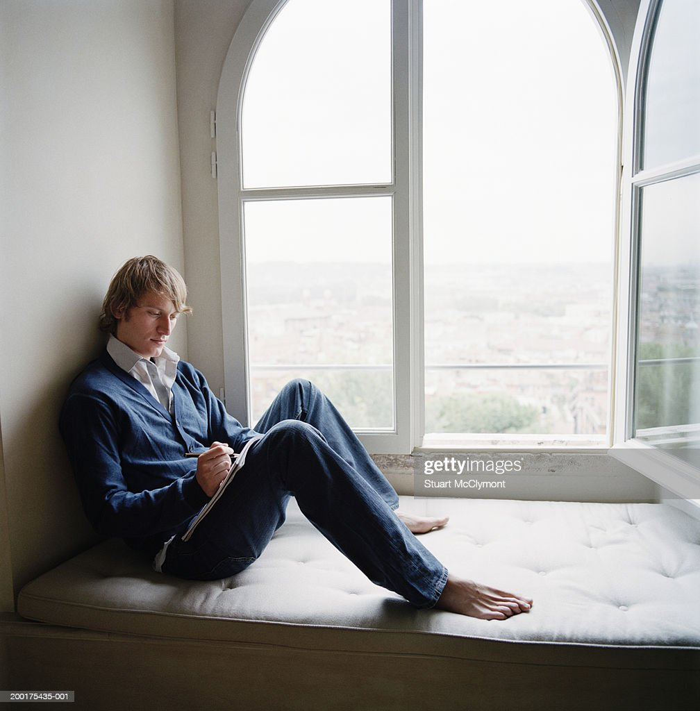 Young Man Sitting On Window Seat Writing On Notepad Side