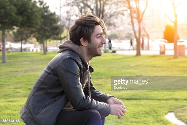 Young Man sitting on wooden bench in city park