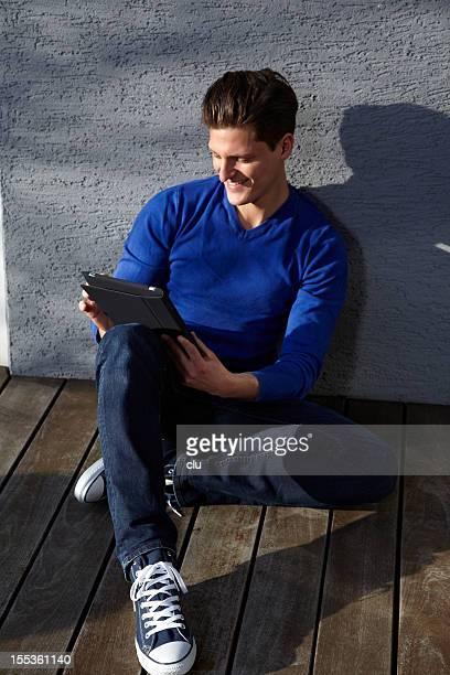Jeune homme assis en plein air sur le sol à l'aide de Tablette numérique