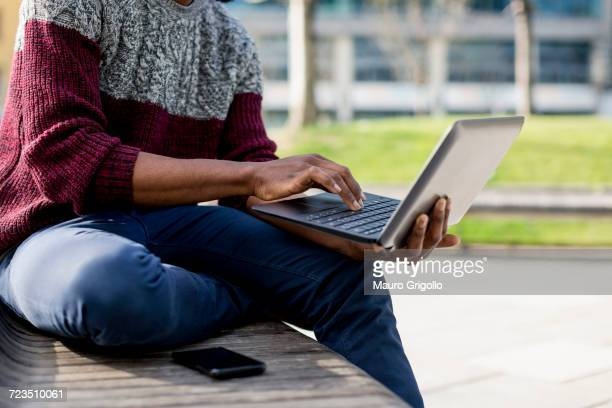 Young man sitting outdoors on bench, using laptop, mid section
