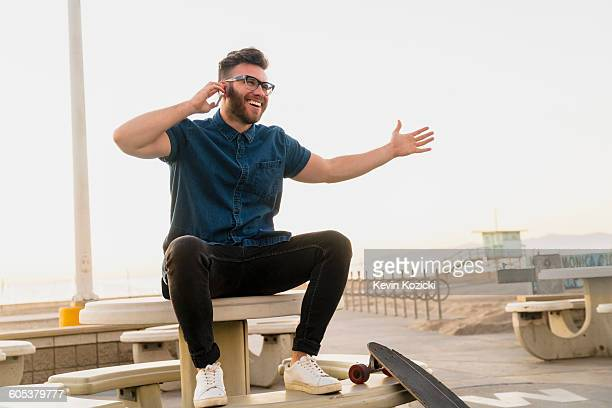 Young man sitting outdoors, using smartphone, laughing