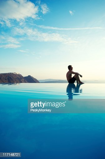 Young Man Sitting Reflecting on Infinity Pool Edge Tourist Resort