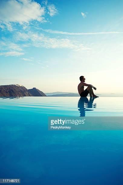 Jeune homme assis reflétant le bord de la piscine à débordement Edge complexe touristique