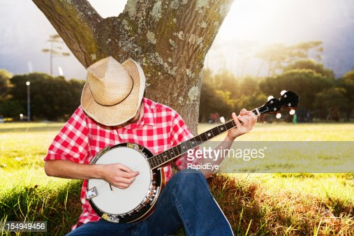 Young man sitting under tree in country playing his banjo