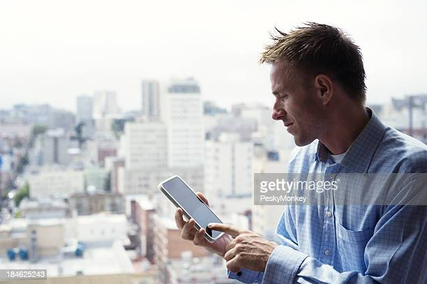 Young Man Sitting Using Small Tablet Computer Above City Skyline