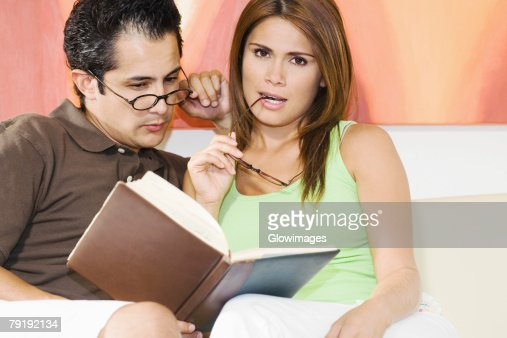 Young man sitting with a young woman reading a book : Foto de stock