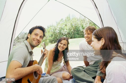 Young man sitting with his friends and playing guitar inside a tent : Stock Photo