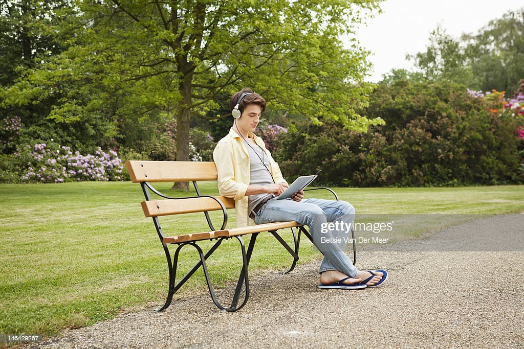 Young man sitting with i pad on park bench.