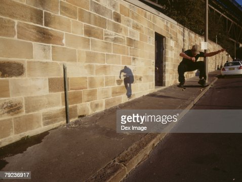 Young man skateboarding down the street : Stock Photo