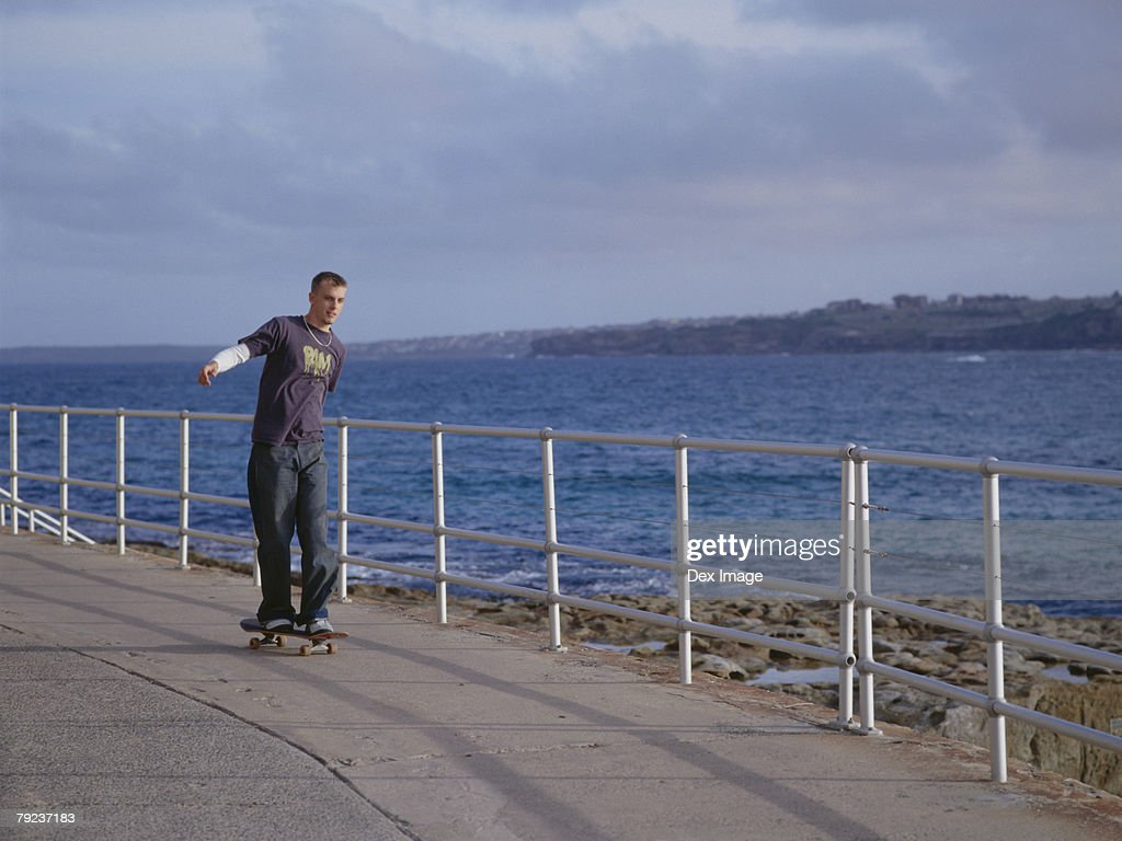 Young man skateboarding on pavement, near sea : Stock Photo
