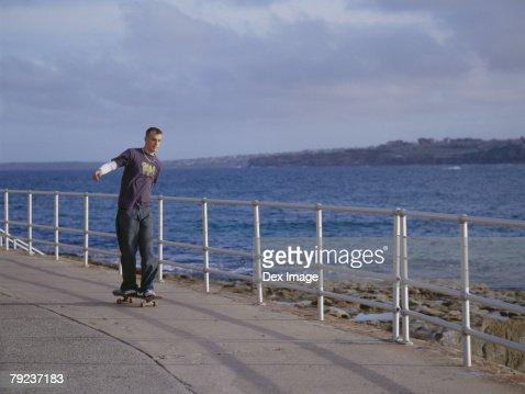 Young man skateboarding on pavement, near sea : Stock Photo