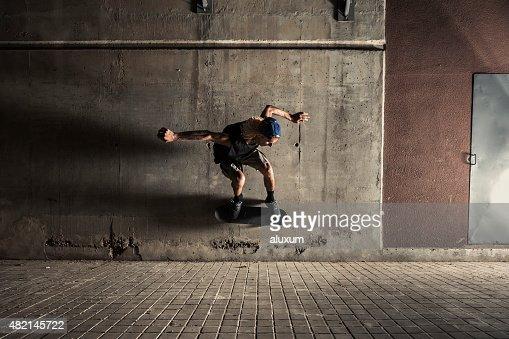 Young man skating in the city at night