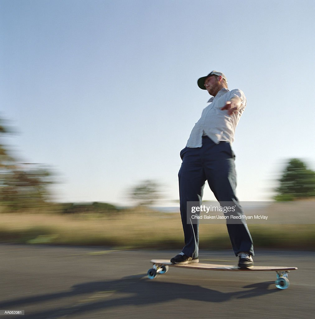 Young man skating on longboard, side view (blurred motion) : Stock Photo