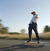 Young man skating on longboard, side view (blurred motion)