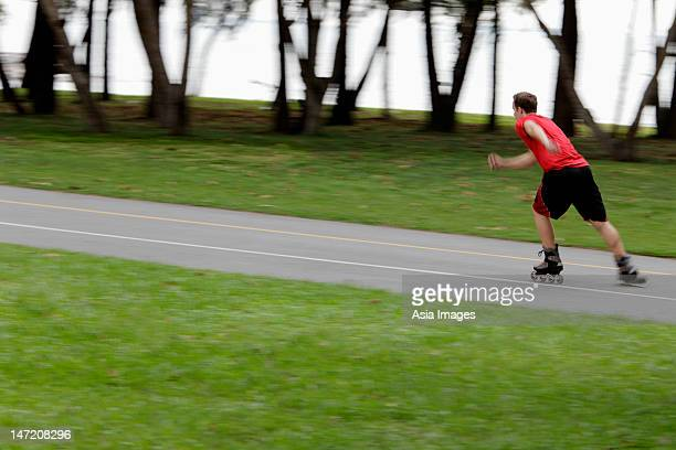 young man skating through park