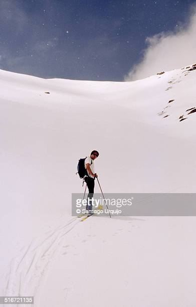 Young man ski mountaineering up a snow slope