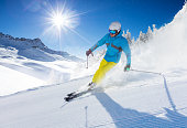 Young man skier running down the slope in Alpine mountains. Winter sport and recreation, leasure outdoor activities.