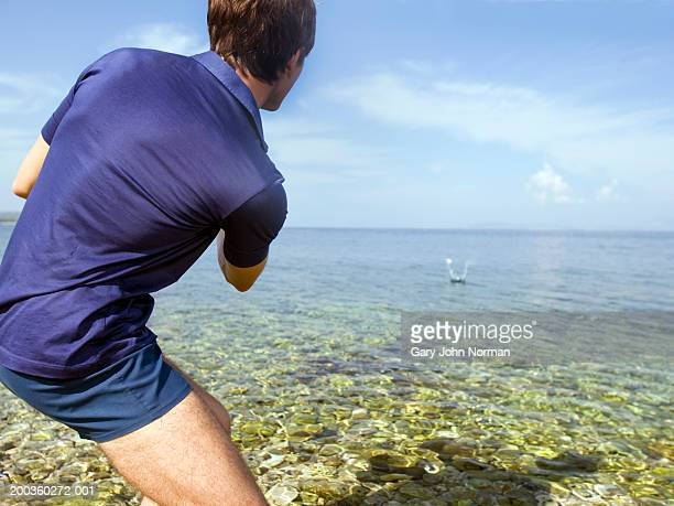 Young man skipping rock in ocean, rear view