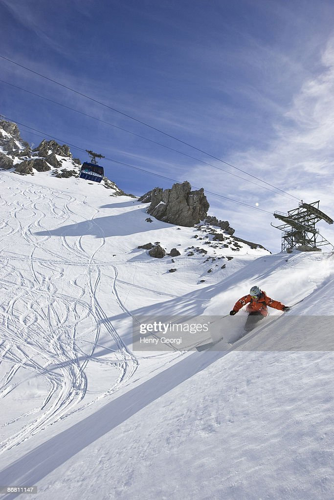 A young man skis untracked powder off-piste at St. Anton am Arlberg, Austria.