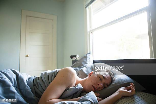 Young Man Sleeping Comfortably in Large Bed