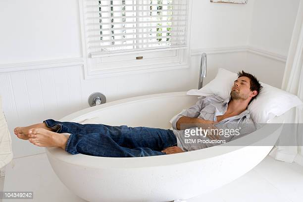 Young man sleeping in bath