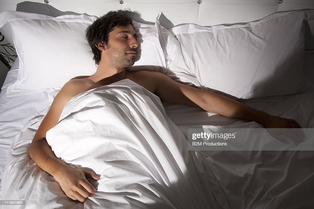 Young man sleeping in bed : Stock Photo