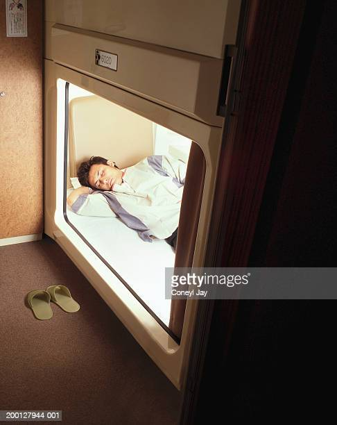 Young man sleeping in capsule hotel, view through opening