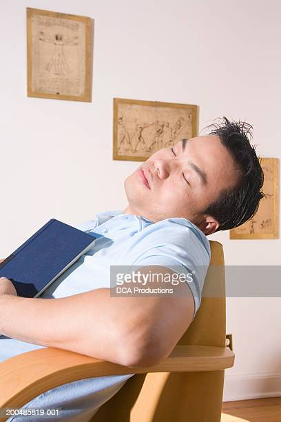 Young man sleeping in chair with book on chest