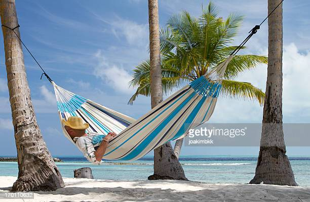 Young man sleeping in hammock by the beach