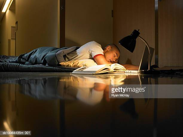 Young man sleeping in sleeping bag on floor with lamp, laptop and open book