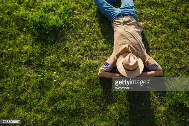 Young man sleeping on a meadow, top view