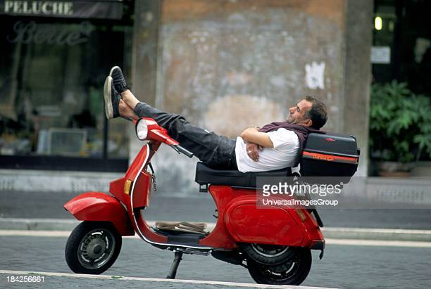 Young man sleeping on red scooter vespa Piazza Navona Rome Italy