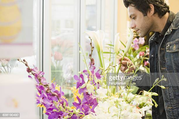 Young man smelling flower in florist shop